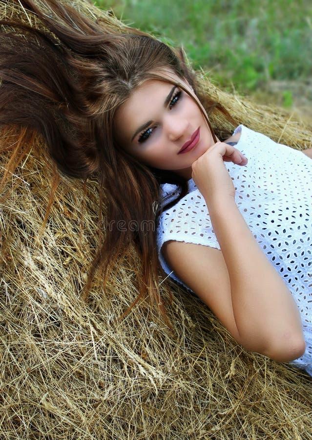 Menina que encontra-se no feno foto de stock royalty free
