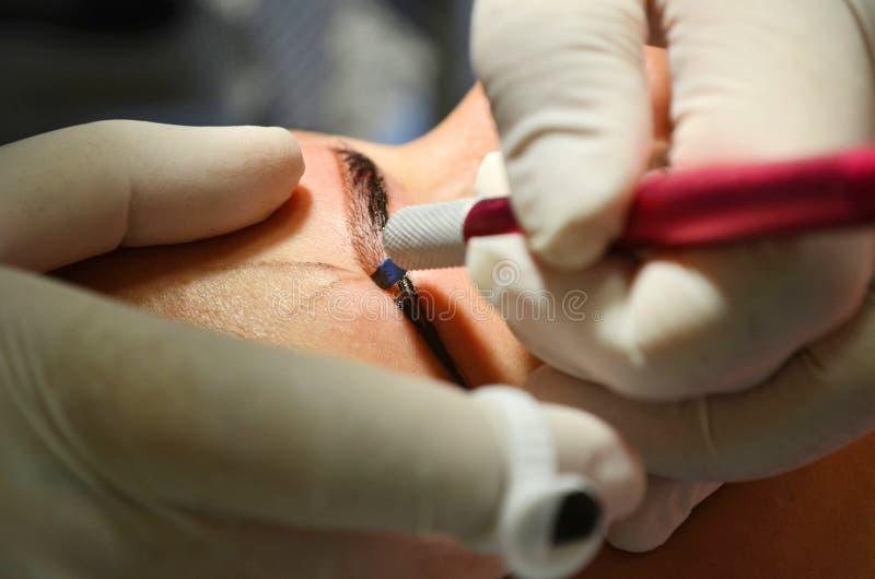 Menina que encontra-se no procedimento de microblading O Cosmetologist nas luvas brancas faz a composição permanente nas sobrance imagens de stock