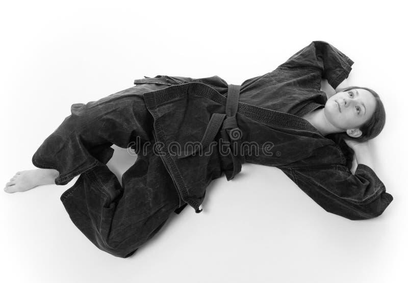 Menina que encontra-se no uniforme preto foto de stock