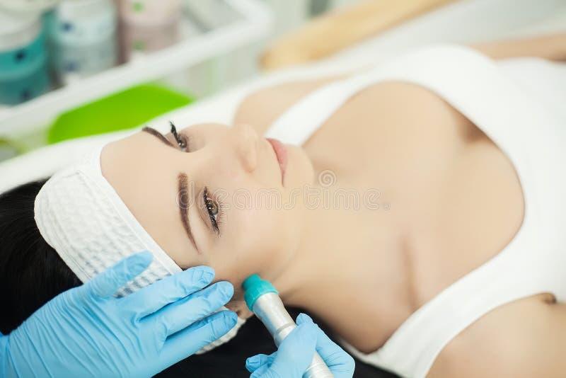 Menina que encontra-se nos termas da beleza que apreciam a terapia da pele usando o tre atual fotografia de stock royalty free