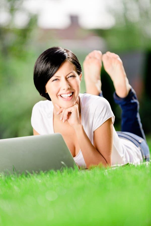 Menina que encontra-se nos trabalhos de grama verde no PC foto de stock