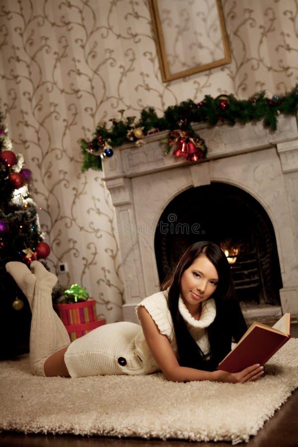 A menina que encontra-se perto da chaminé e lê um livro fotografia de stock