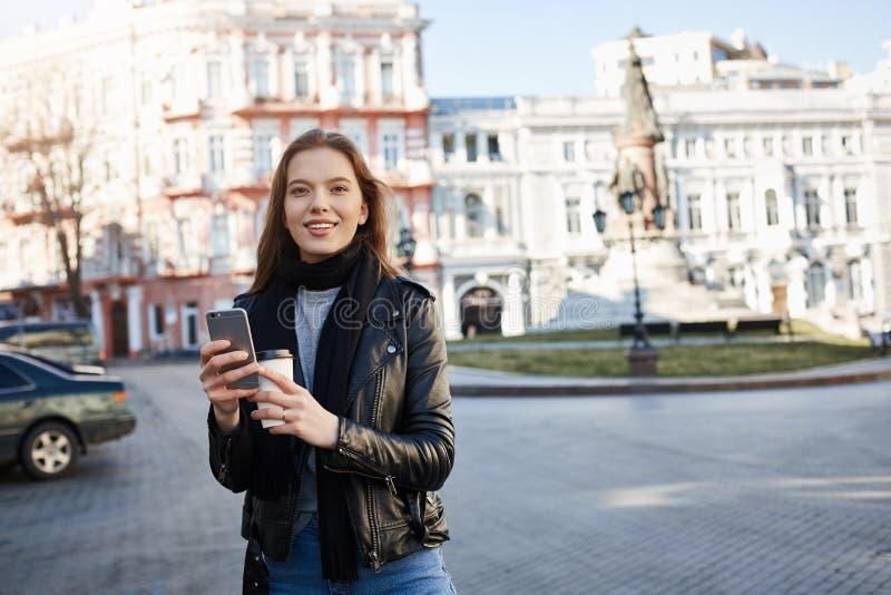 Menina que encontra sua maneira na cidade Retrato da fêmea caucasiano encantador no equipamento na moda que anda na rua, sorrindo imagens de stock