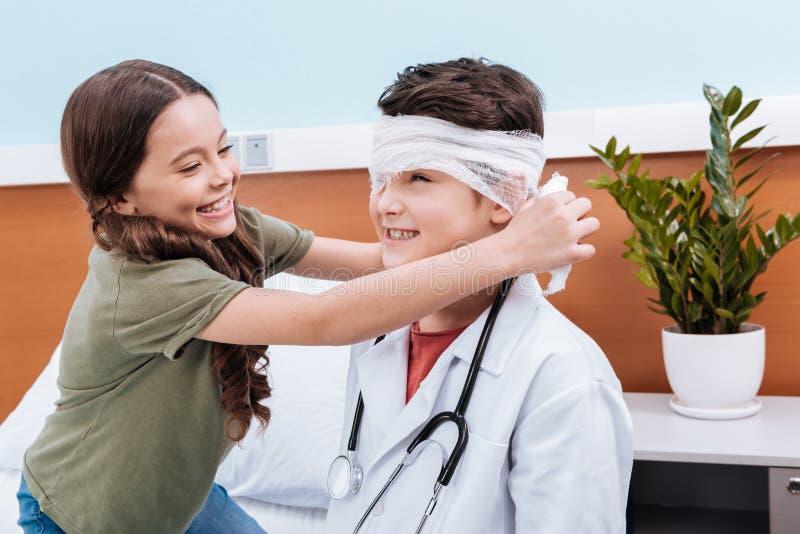 menina que enfaixa a cabeça do doutor do menino fotografia de stock
