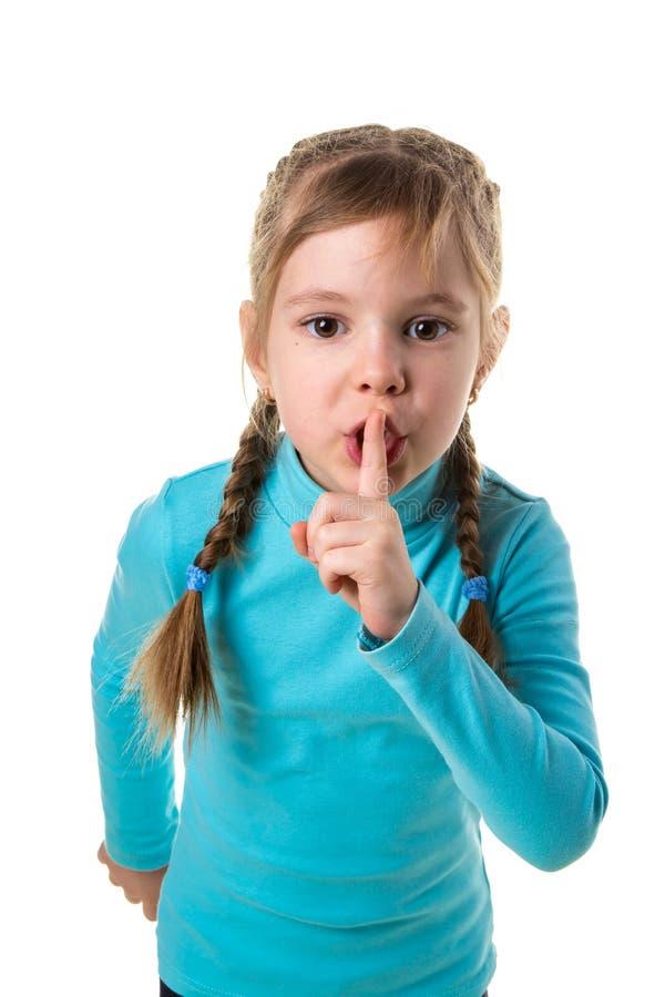 Menina que engana ao redor e para apontar o dedo para ser fundo isolado quieto, branco do retrato fotografia de stock