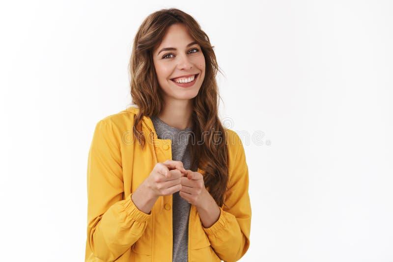 Menina que envia a felicitações o Penteado encaracolado satisfeito amigável da jovem mulher orgulhosa bonita que aponta a câmera fotos de stock royalty free