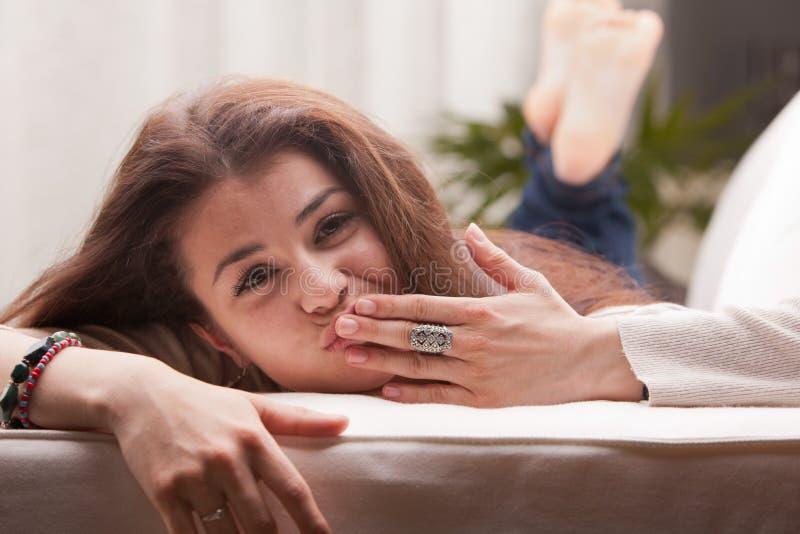 Menina que envia levemente pouco beijo em um sofá fotos de stock