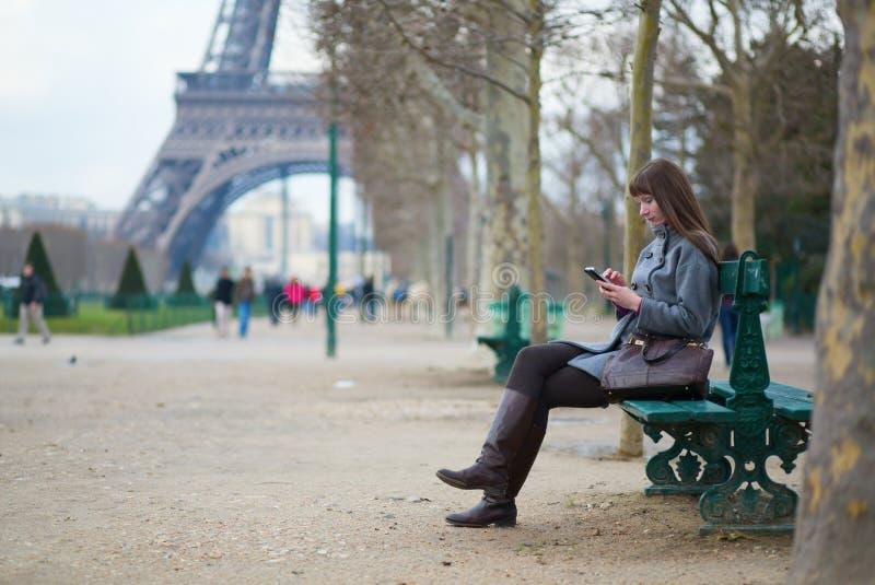 Menina que envia sms ou que surfa na rede fotografia de stock