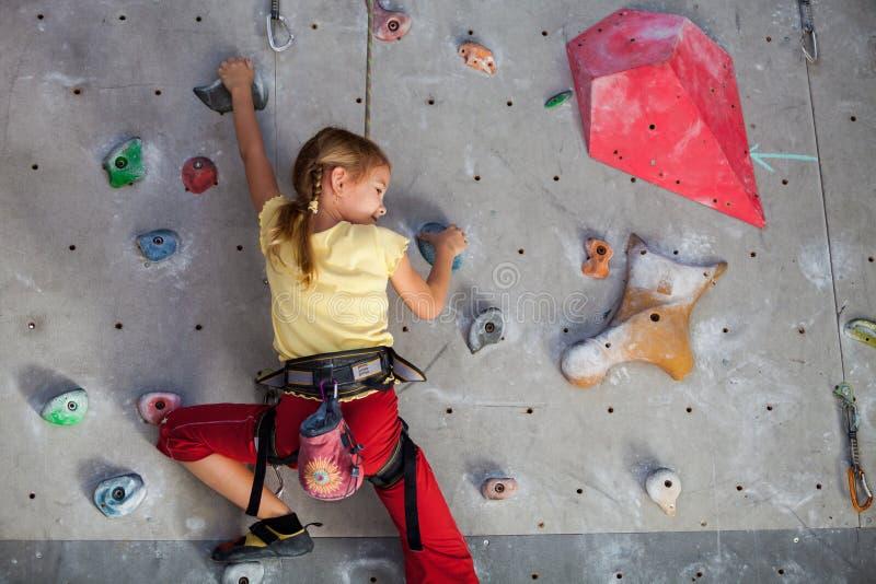 Menina que escala uma parede da rocha interna imagem de stock