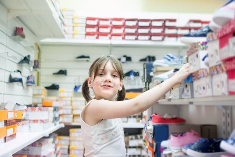 Menina que escolhe sapatas na loja fotos de stock royalty free