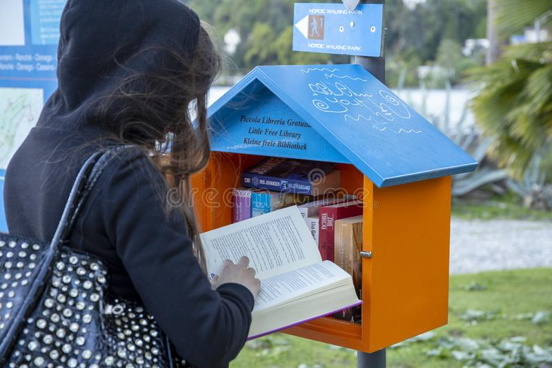 Menina que escolhe um livro ler de uma biblioteca pequena para livre fotografia de stock