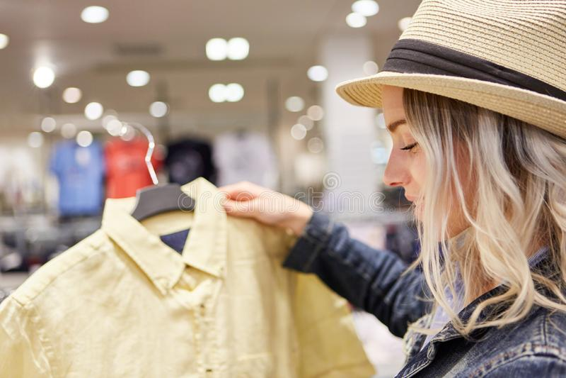 Menina que escolhe uma blusa na loja fotos de stock royalty free