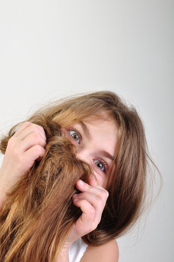 Menina que esconde atrás de seu cabelo imagem de stock royalty free