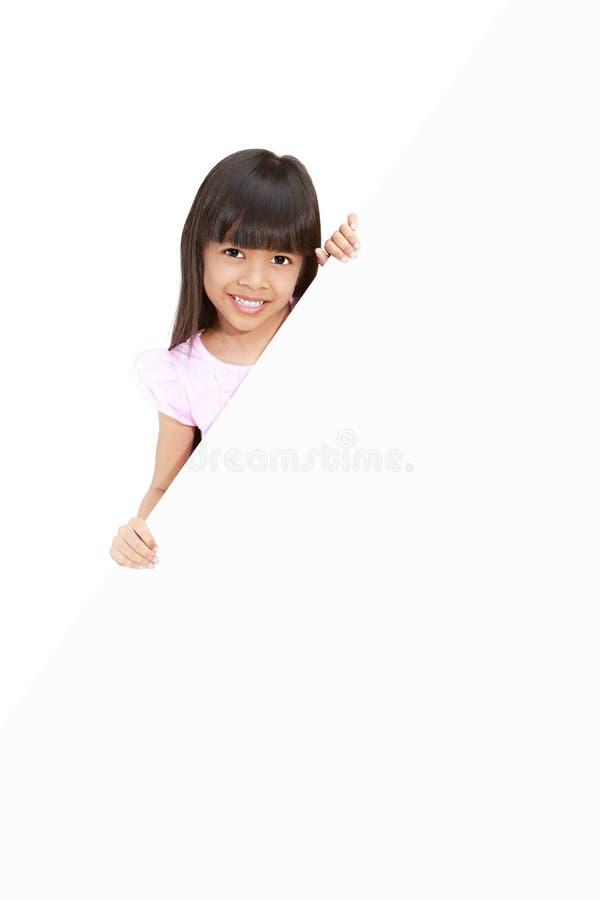 Menina que esconde atrás de uma placa branca imagens de stock royalty free