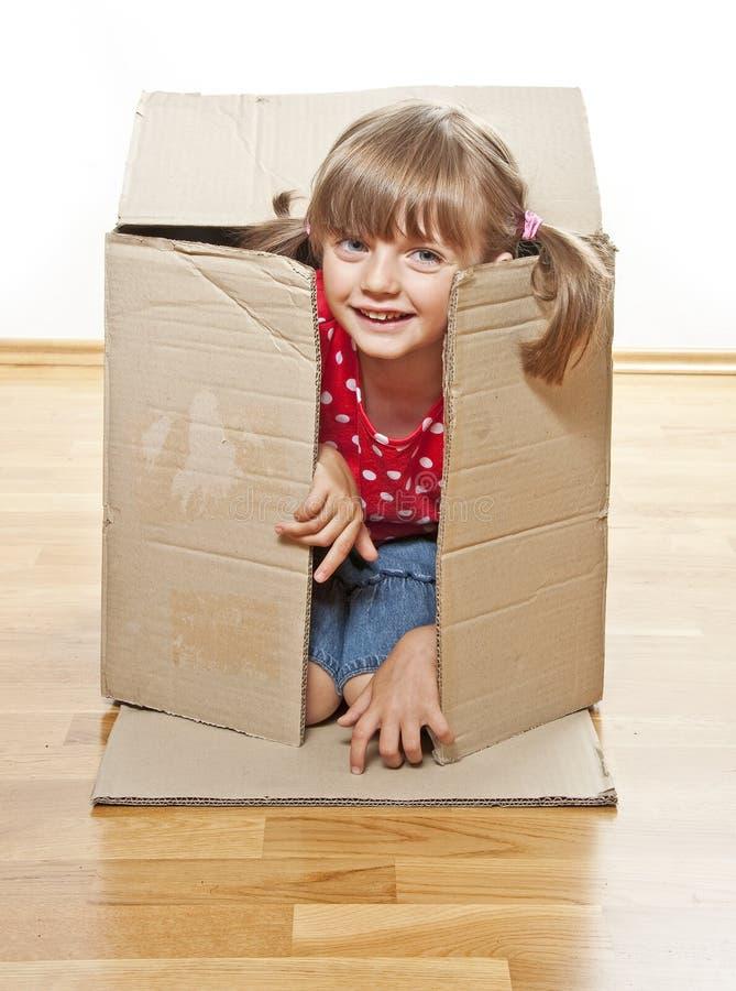 Menina que esconde a caixa de papel interna imagem de stock