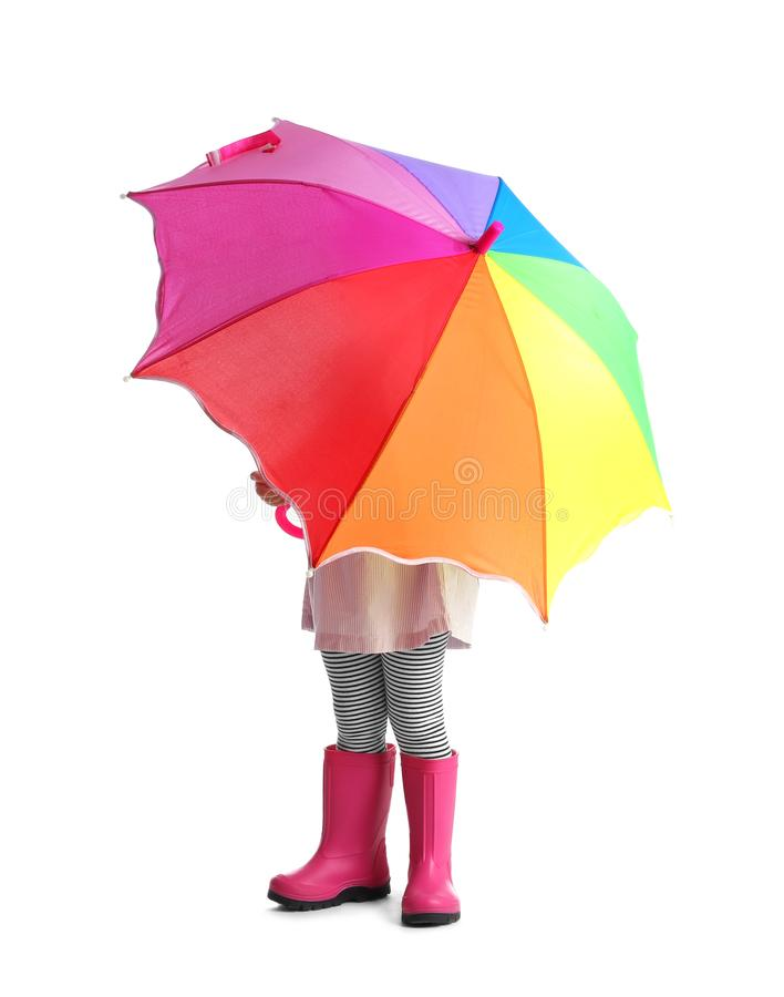 Menina que esconde sob o guarda-chuva do arco-íris fotos de stock