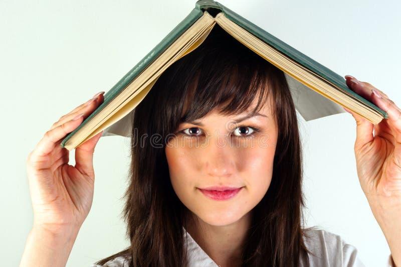 Menina que esconde sob o livro imagem de stock