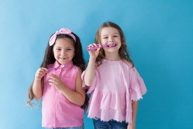 Menina que escova seus dentes com um dente da escova de dentes imagem de stock