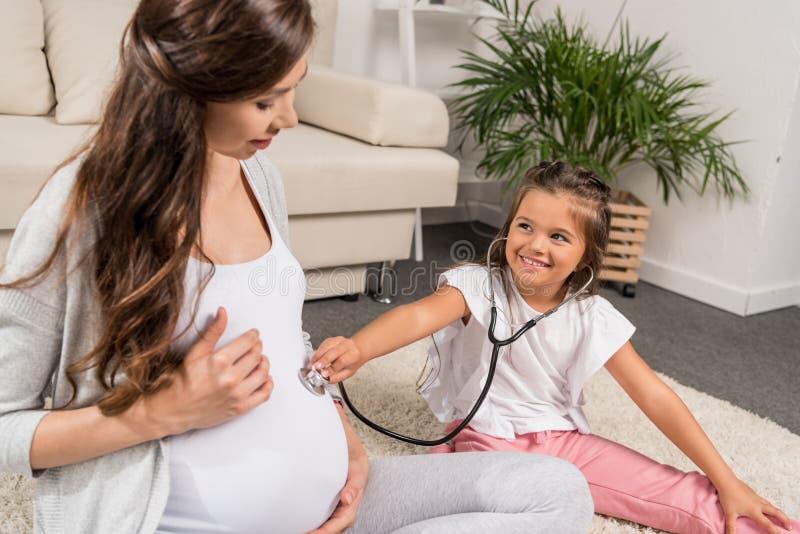 Menina que escuta a barriga grávida através do estetoscópio fotos de stock