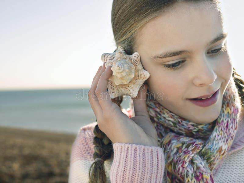 Menina que escuta a concha do mar na praia imagem de stock royalty free