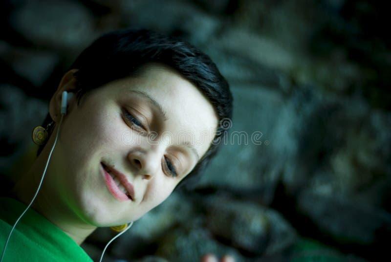 Menina que escuta a música foto de stock