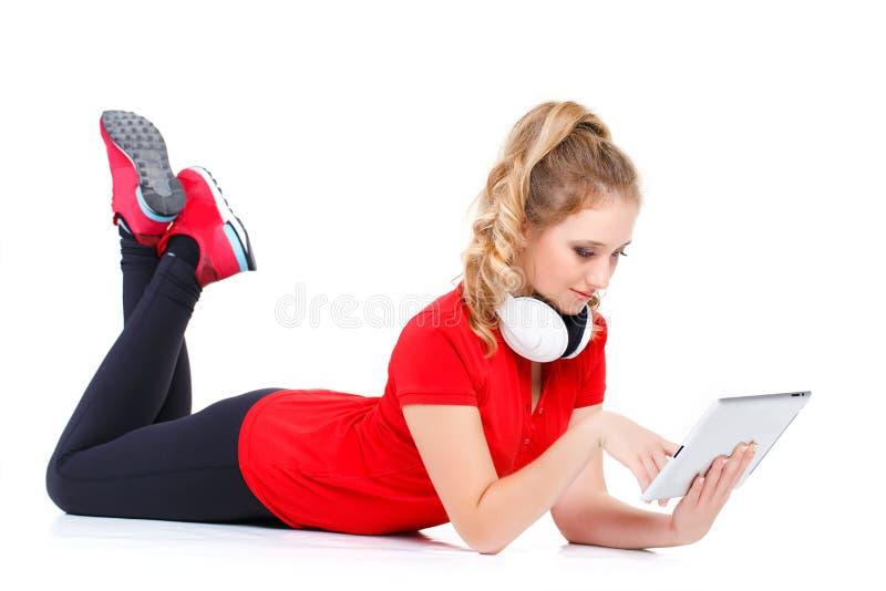 Menina que escuta a música em um tablet pc imagem de stock