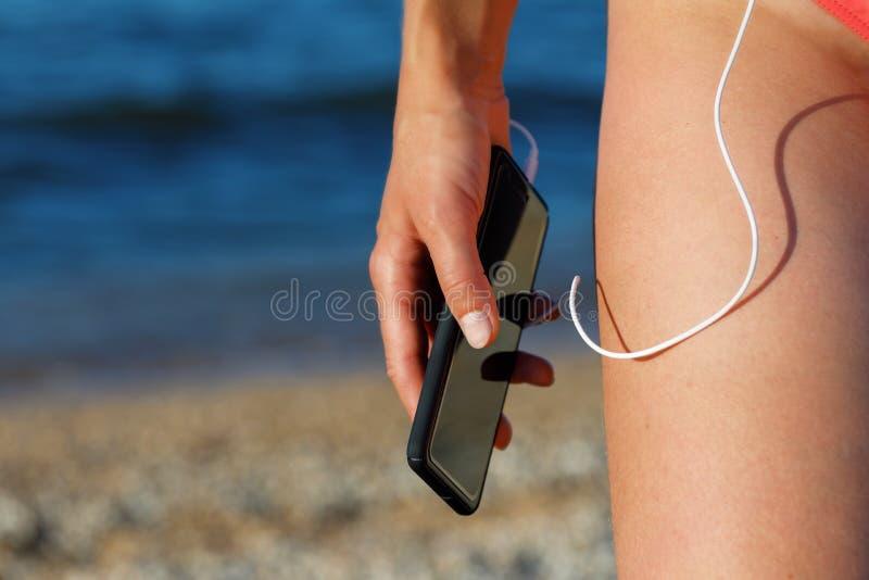 Menina que escuta a música na praia imagem de stock