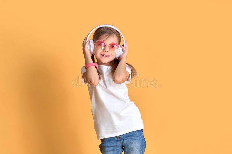 Menina que escuta a música nos fones de ouvido no fundo amarelo Criança bonito que aprecia a música de dança feliz no fundo do es fotografia de stock
