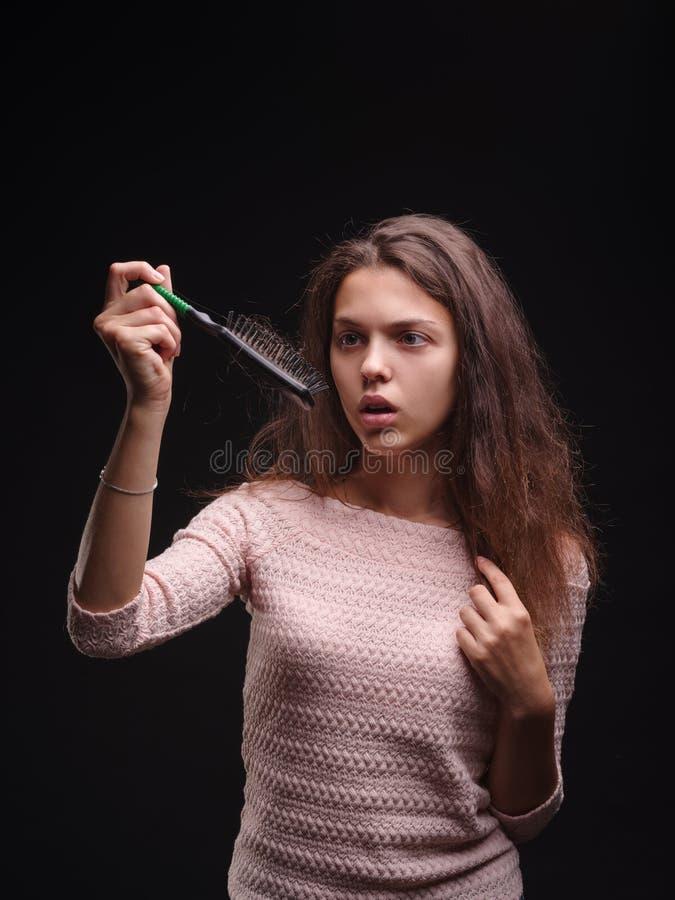 Menina que esforça-se com o cabelo tangled no fundo preto Mulher do close-up que olha um pente com cabelo Conceito calvo fotografia de stock