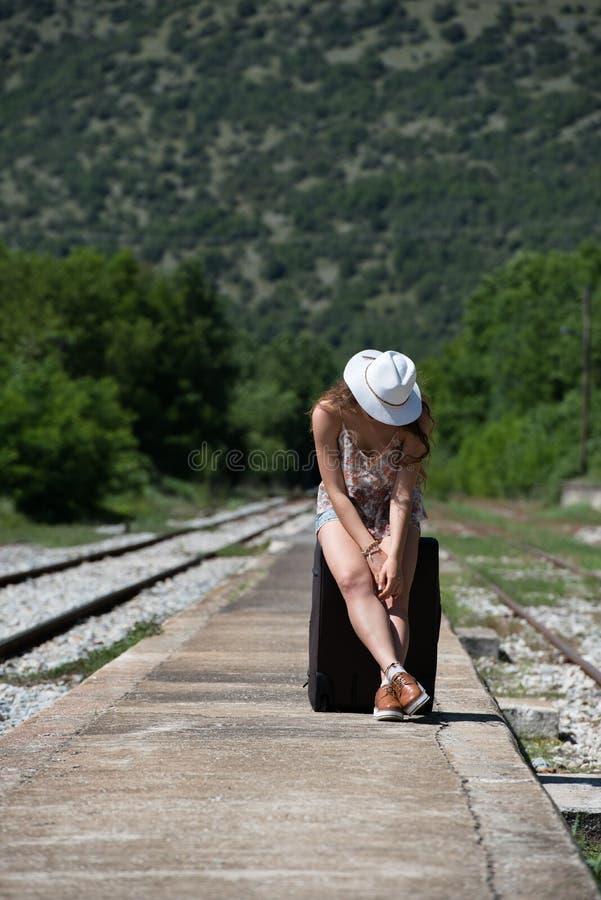 Menina que espera com rolamento da mala de viagem ereta em docas fotos de stock royalty free
