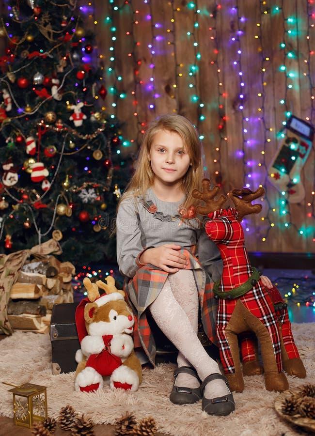 Menina que espera um milagre em decorações do Natal fotografia de stock royalty free