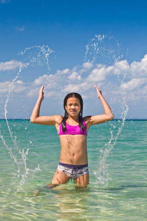 Menina que espirra na água na praia foto de stock royalty free