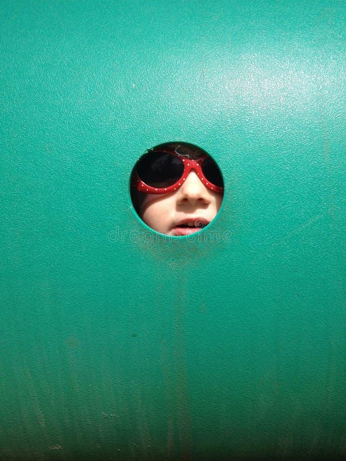 Menina que espreita através do furo na parede verde fotografia de stock royalty free