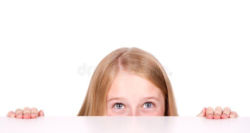 Menina que espreita da tabela de trás foto de stock royalty free