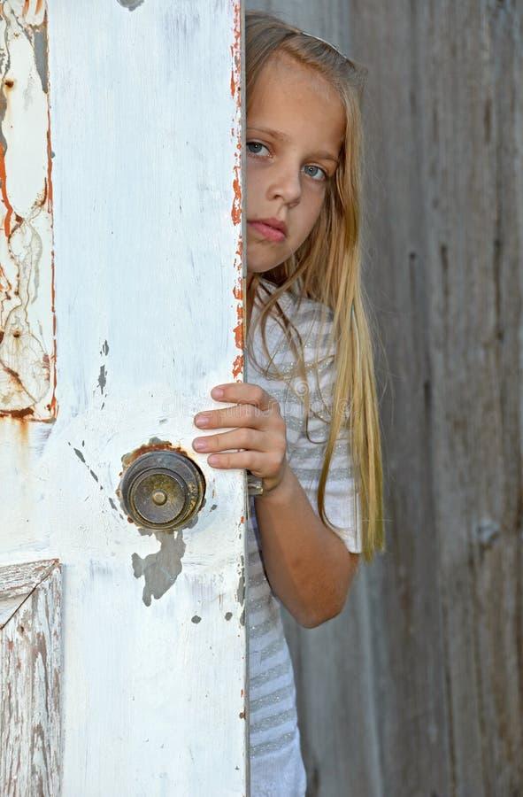 Menina que espreita em torno da porta foto de stock