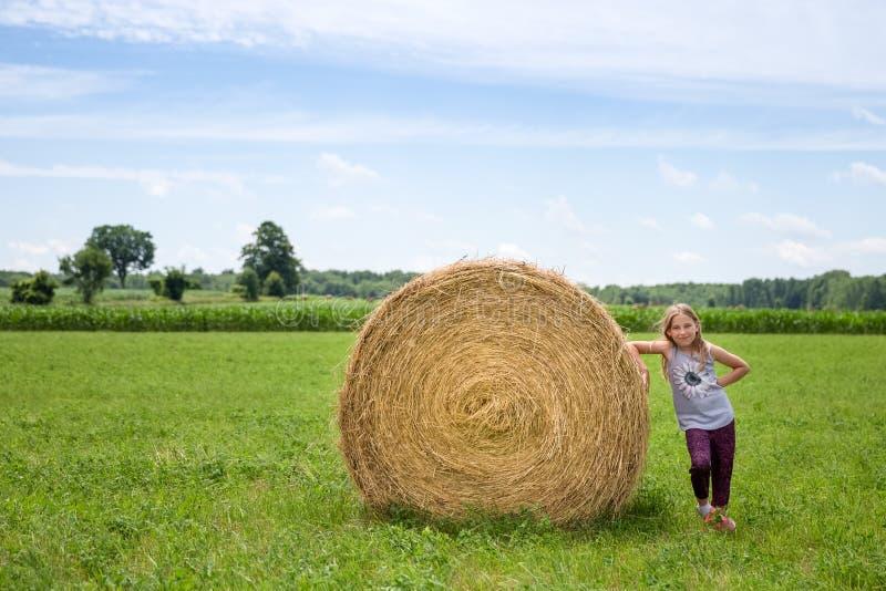 Menina que está ao lado de Hay Bale em um campo verde fotografia de stock