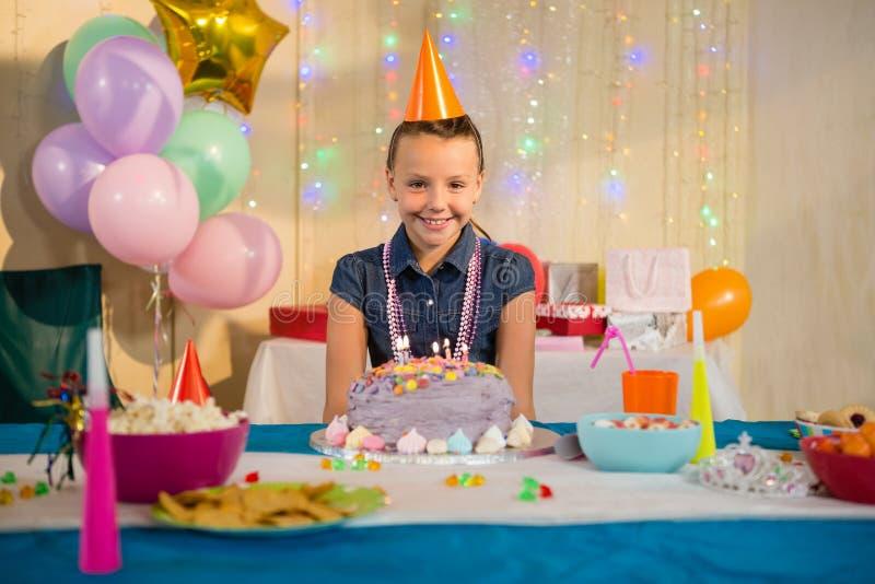 Menina que está com bolo de aniversário em casa fotos de stock royalty free