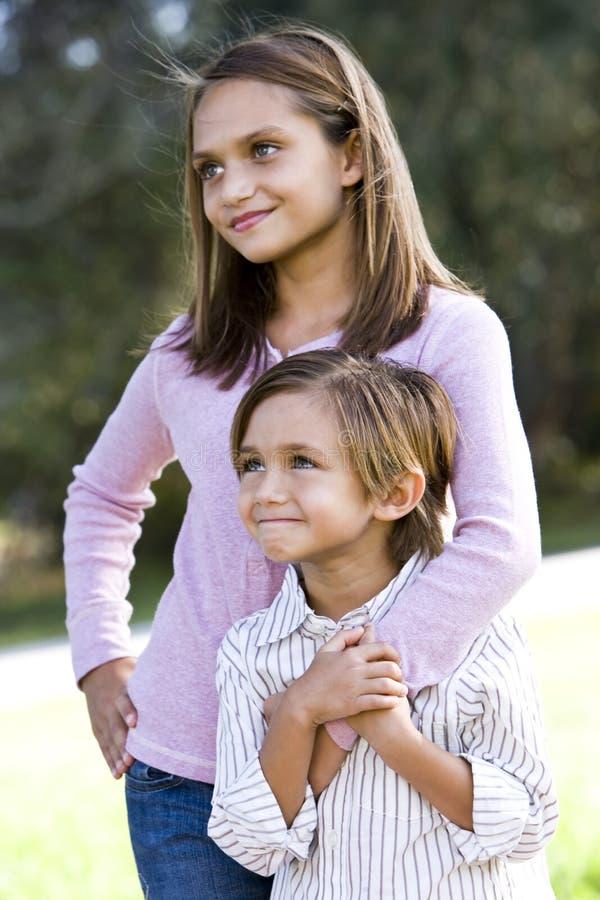 Menina que está com irmão pequeno ao ar livre imagem de stock