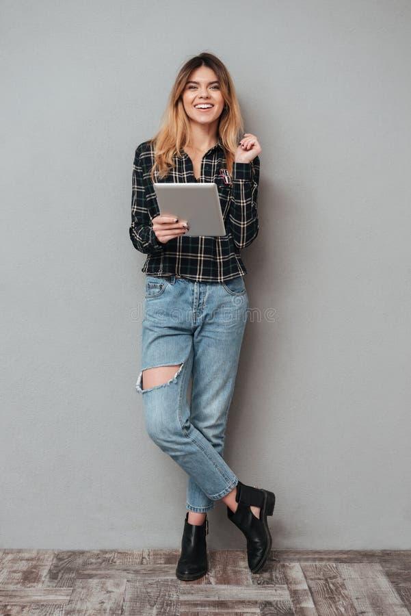 Menina que está e que guarda o tablet pc sobre o fundo cinzento fotografia de stock