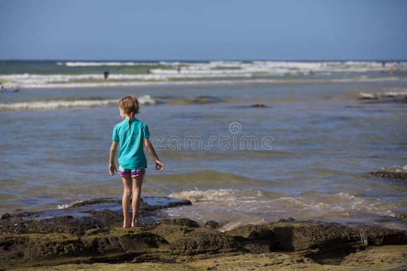 Menina que está em rochas no mar fotos de stock royalty free