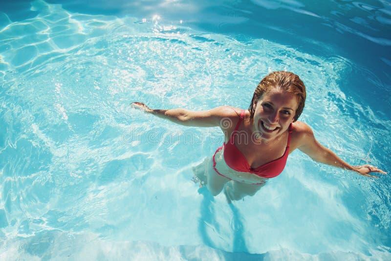 Menina que está em um sorriso da piscina foto de stock