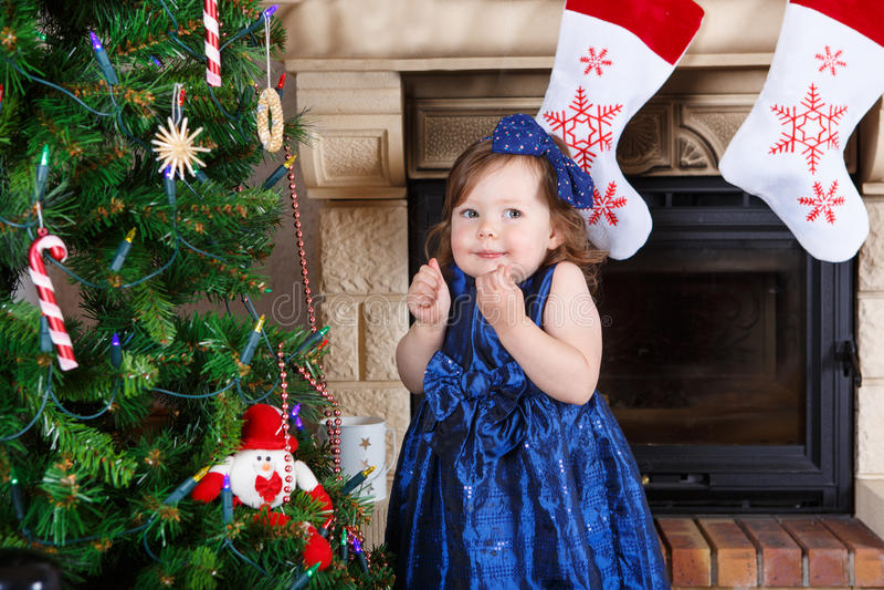Menina que está feliz sobre a árvore e as luzes de Natal fotos de stock