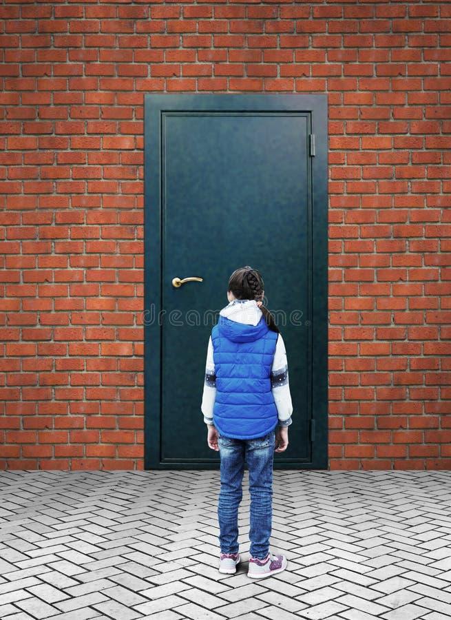 Menina que está na frente de uma parede de tijolo com a porta fechado do metal sem sinais imagem de stock royalty free
