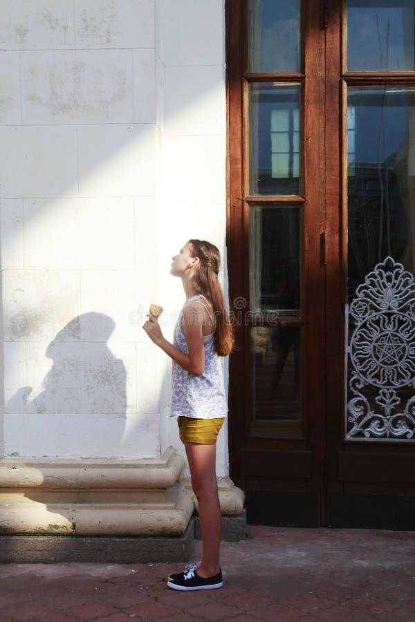 Menina que está na luz solar perto da construção fotos de stock royalty free