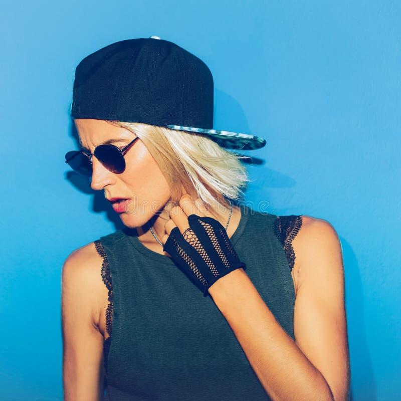 Menina que está na parede azul em vidros e no tampão à moda chiqueiro urbano fotografia de stock royalty free
