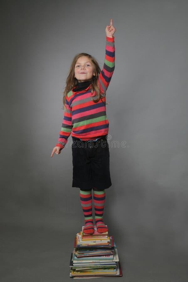 Menina que está na pilha dos livros fotografia de stock royalty free