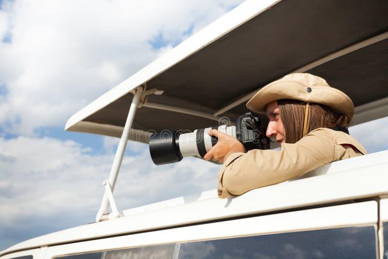 Menina que está no jipe aberto do safari do telhado com câmera imagens de stock