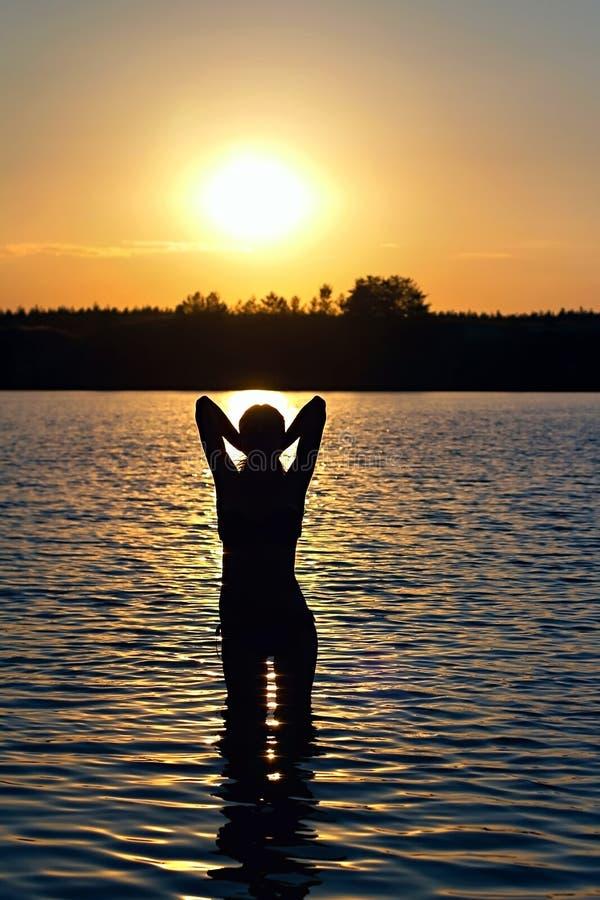 Menina que está no lago no por do sol fotografia de stock