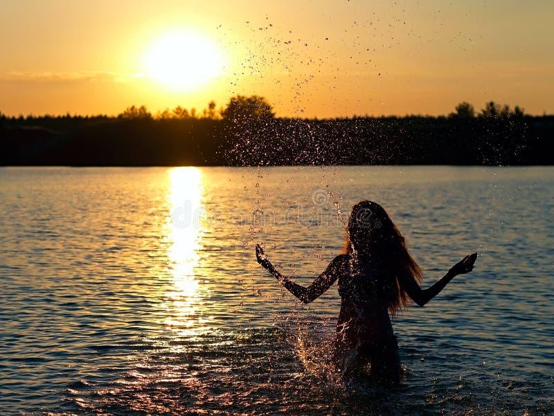 Menina que está no lago no por do sol fotos de stock royalty free