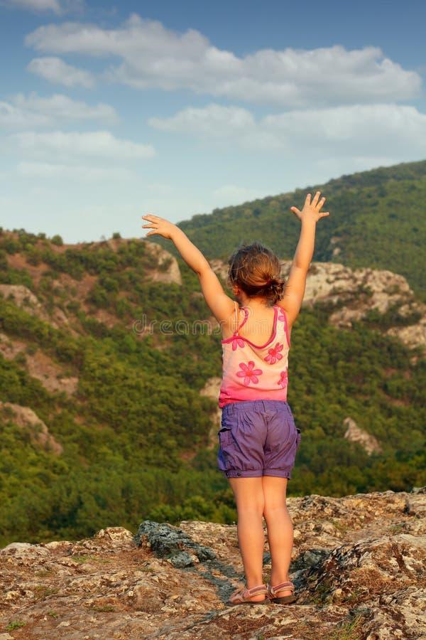 Menina que está no pico de montanha fotografia de stock